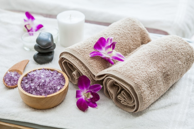 Beautiful spa composition treatment setting  orchid, towels, bath salts , candle, stone