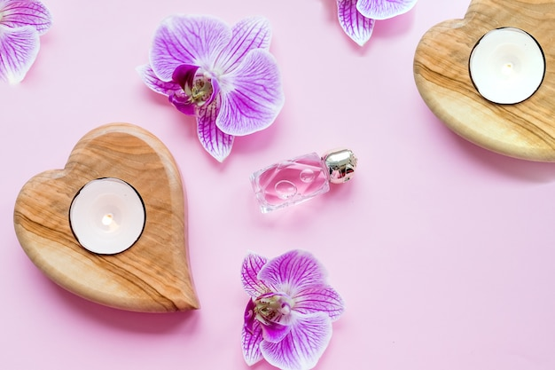 Beautiful spa composition.wellness and spa composition with perfum, burning candles and orchid flowers on pink