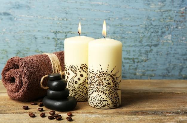 木製のテーブルの上に、装飾的なインドのキャンドルと美しいスパ構成