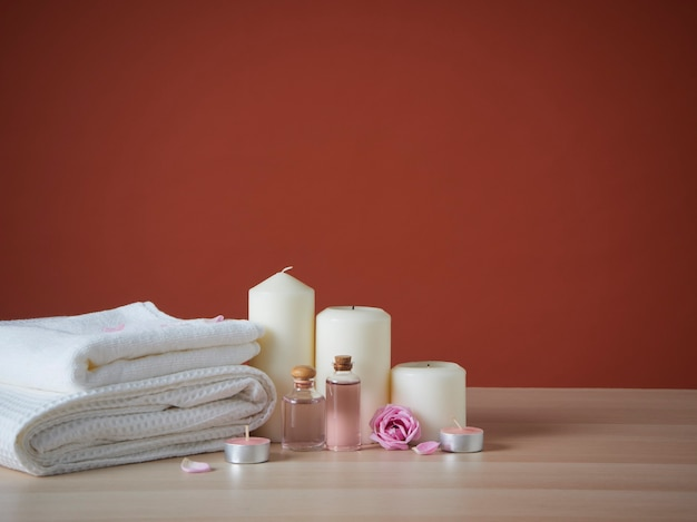 Beautiful spa composition with scented candles and roses on table