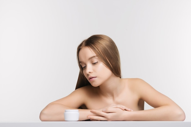 Beautiful spa girl with jar of cream isolated on white