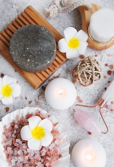 Beautiful spa relax concept. handmade soap, jade roller and sea salt on grey stone background.