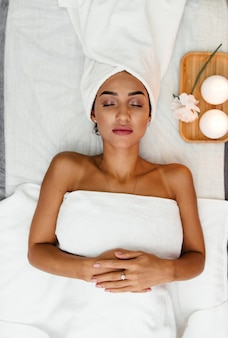 Beautiful spa woman lying on towel in spa salon.