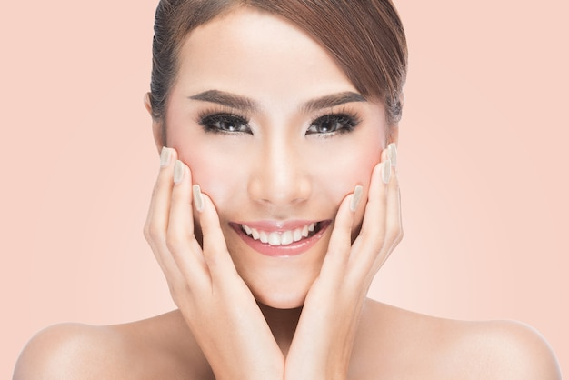 Beautiful spa woman touching her face,on pink background with clipping path.