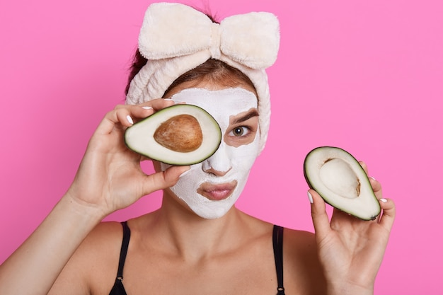 Beautiful spa woman with facial mask on face and holding halves of avocado in hands, looking at camera, doing cosmetology procedures at home, wearing hair band with bow.