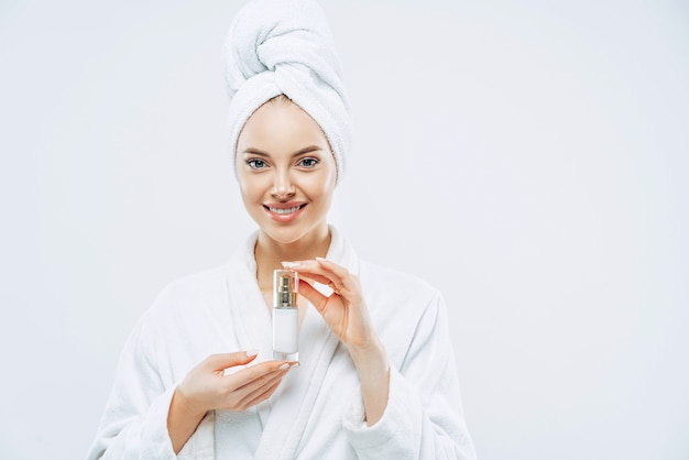 Beautiful spa young woman with healthy fresh skin applies anti aging lotion or cosmetic cream, uses day moisturizer, stands indoor, dressed in bath robe and towel, takes shower before going out