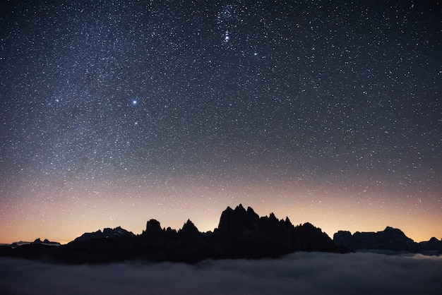 Beautiful space filled with stars in the sky. the mountains are surrounded by dense fog.