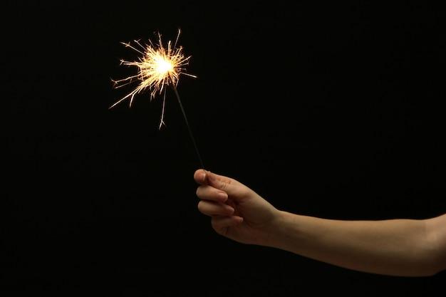 黒い表面に女性の手の美しい線香花火