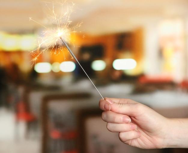 部屋の上の女性の手の美しい線香花火