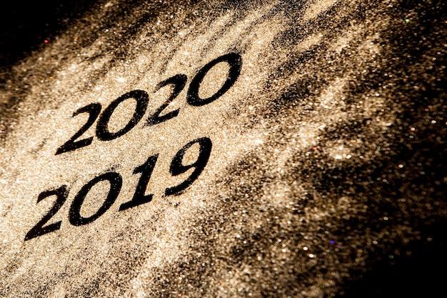 Красивые сверкающие золотые числа с 2019 по 2020 год на черном фоне для дизайна