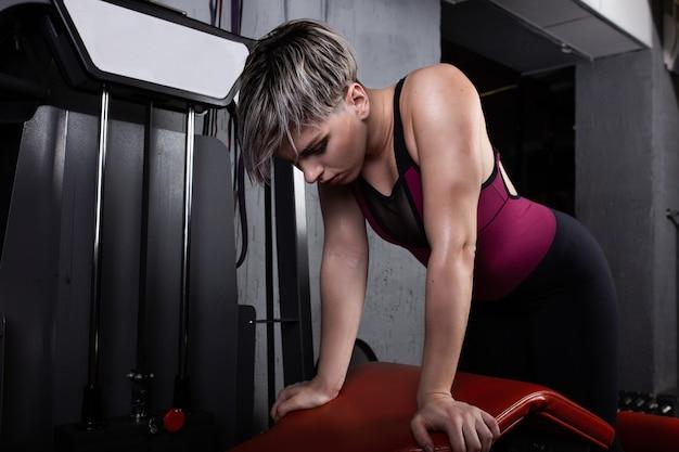 아름다운 스포츠 소녀는 체육관에서 시뮬레이터에 종사