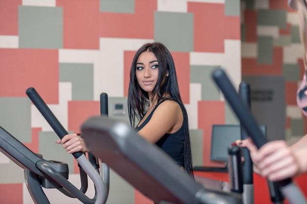 Красивая спортивная брюнетка женщина упражняется с помощью эллиптической машины рядом с нужным человеком и улыбается ему во время тренировки в современном тренажерном зале