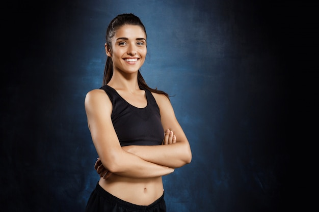 Beautiful sportive girl posing with crossed arms over dark wall.