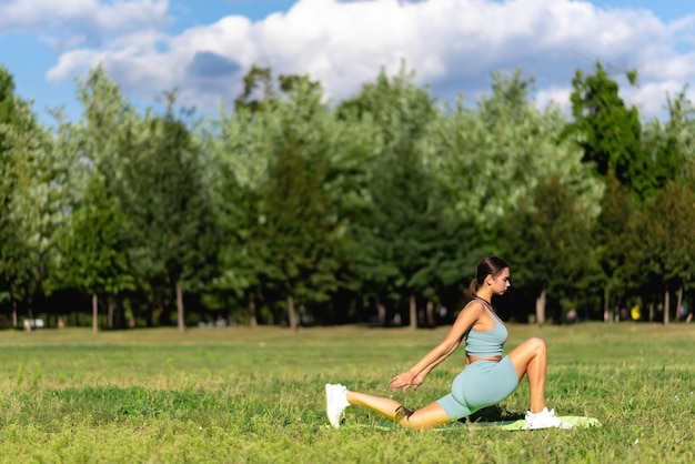 A beautiful sportive girl in sportswear practices yoga on the green grass in the city park. flexible female circus gymnast, gymnastic handstand, young acrobat standing on hands, yoga