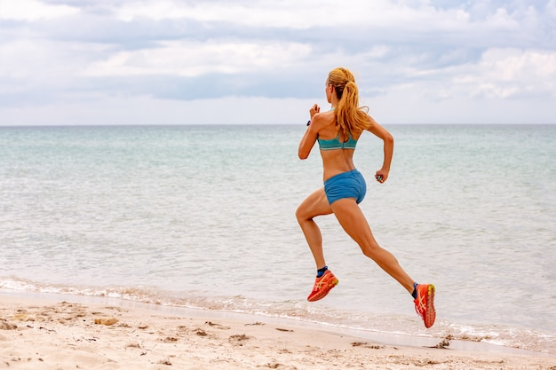 Beautiful sportive woman running along beautiful sandy beach, healthy lifestyle, enjoying active summer vacation near the sea