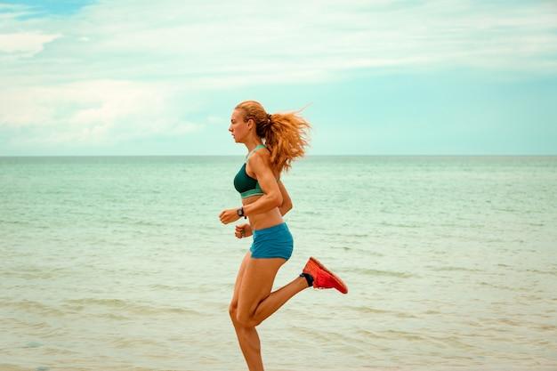 美しい砂浜のビーチ、健康的なライフスタイルに沿って実行している、海の近くのアクティブな夏休みを楽しんでいる陽気な美人