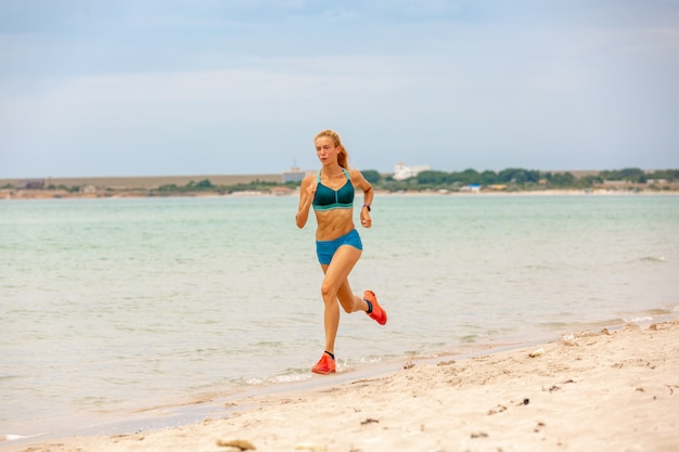 美しい砂浜、健康的なライフスタイルに沿って実行している美しい陽気な女性、海の近くのアクティブな夏休みを楽しんでいます