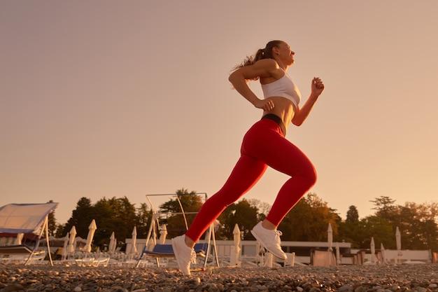 Красивый спортивный силуэт женщины в спортивной одежде, бегающей на утреннем рассвете