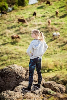Beautiful sportive woman standing on rock field with cows background.
