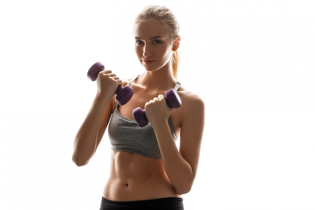 Beautiful sportive woman training with dumbbells