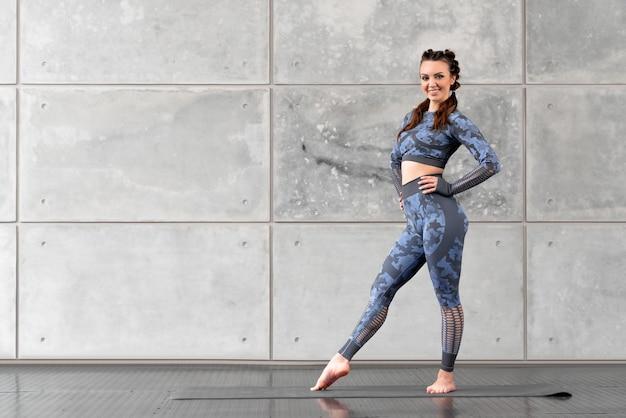 Красивая спортивная фитнес-девушка с косичками позирует, улыбаясь на фоне серой каменной стены. камуфляжный синий спортивный костюм. свободное место для текста. спорт и здоровье