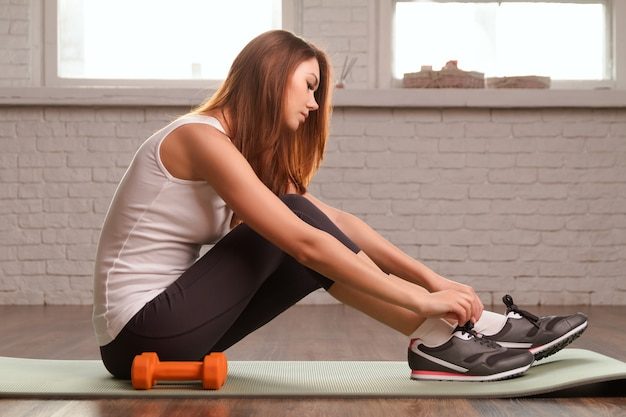 美しいスポーツの女の子はジムで運動をします。やわらかい光