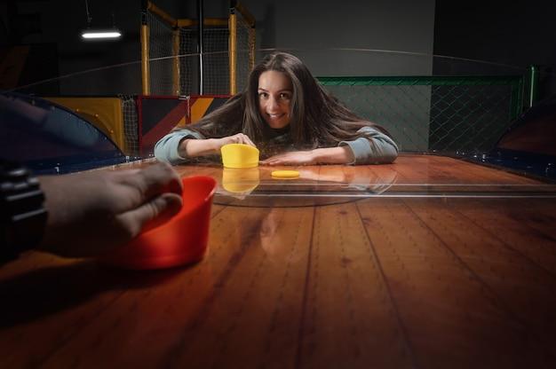 Красивая спортивная девушка играет в воздушный хоккей в развлекательном центре. детский парк. семейный отдых. смешанная техника