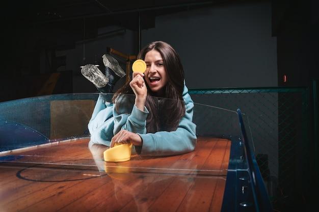 Красивая спортивная девушка играет в воздушный хоккей в развлекательном центре