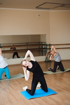 Beautiful sports people are doing exercises and smiling while working out in the gym.