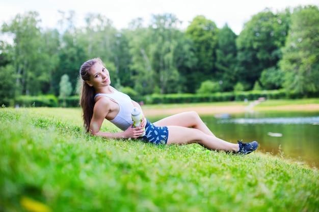 Красивая спортивная женщина, сидящая на траве и держащая воду после тренировки.