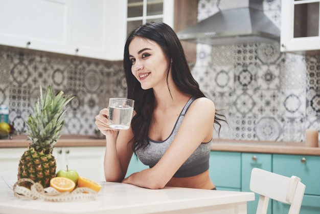 A beautiful sports woman with fresh fruits and vegetables in the kitchen