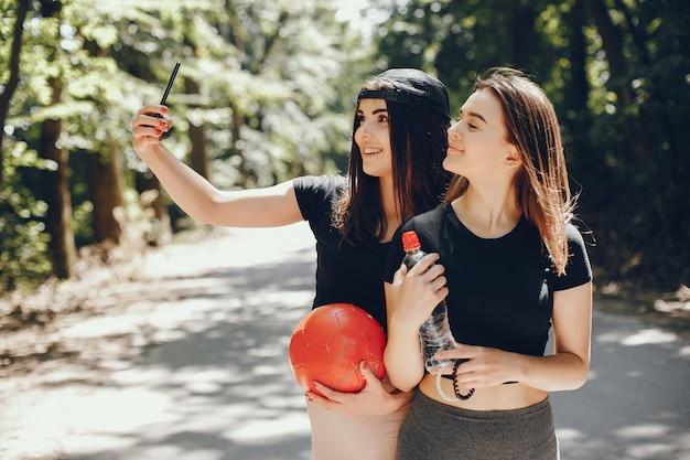 Beautiful sportsgirls in a summer sunny park
