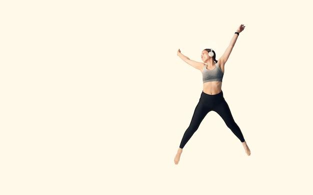 美しいスポーツウーマンが星のように高くジャンプしています。全身写真。