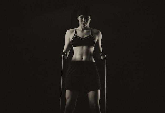 Красивая спортсменка разминает в тренажерном зале со скакалкой