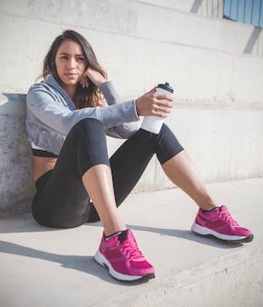Красивая спортсменка отдыхает после тренировки
