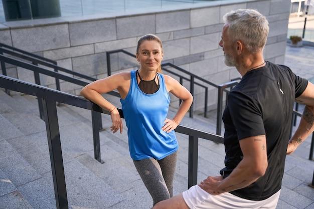 Красивая спортсменка улыбается в камеру, отдыхая вместе со своим мужем или другом стоя