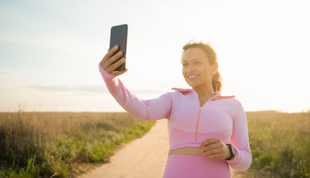 Beautiful sportswoman stands on a deserted steppe road with a smartphone in her hand and cute smiles enjoying the cardio workout outdoor. sport, workout and training concepts outdoors