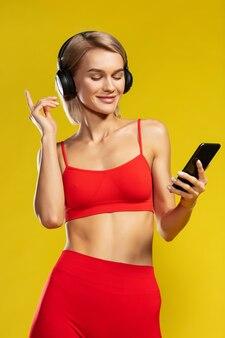 立っている間目を閉じて音楽を聴く赤いスポーツウェアの美しいスポーティなブロンドの女性