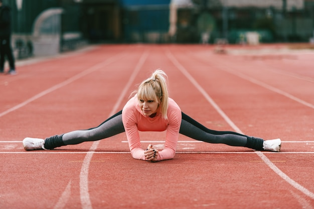 Beautiful sporty caucasian blonde woman in sportswear doing spreads on the racetrack.