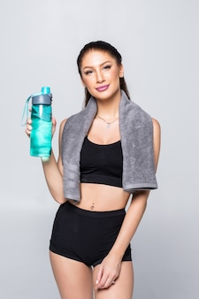 Красивая sporty кавказская женщина держа стекло воды изолированный