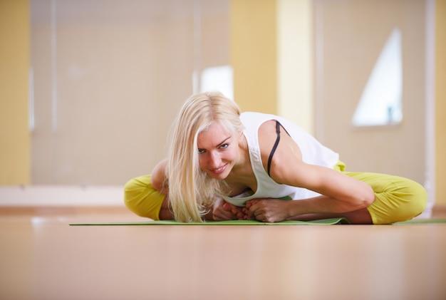 Beautiful sporty fit yogi woman practices yoga asana adho mukha baddha konasana - butterfly pose in the fitness room