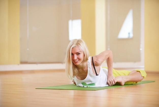 Beautiful sporty fit yogi woman practices yoga asana bhekasana - frog pose in the fitness room