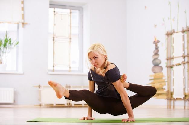 美しいスポーティなフィットヨギ女性がフィットネスルームでヨガのアーサナエカハスタブジャサナポーズを練習します