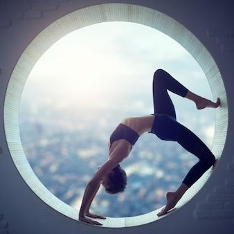 Beautiful sporty fit yogi woman practices yoga asana eka pada urdhva dhanurasana in a round window