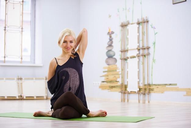 Красивая спортивная девушка-йога занимается йогой в позе орла гарудасана в тренажерном зале