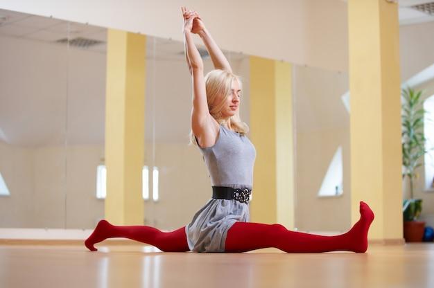 Beautiful sporty fit yogi woman practices yoga asana hanumanasana - monkey pose in the fitness room