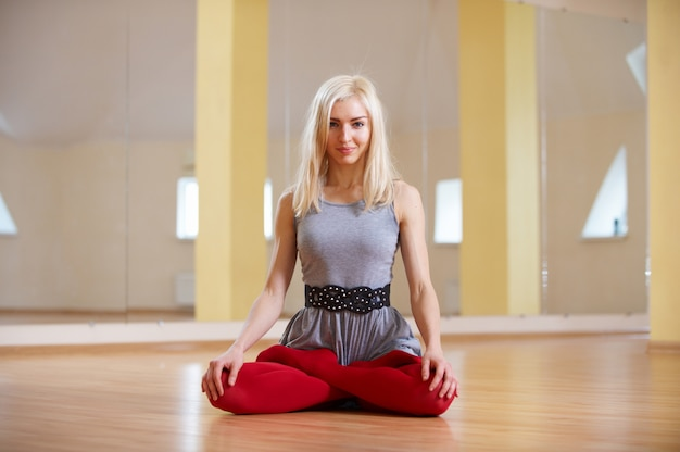Beautiful sporty fit yogi woman practices yoga asana padmasana - lotus pose in the fitness room