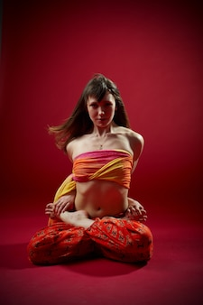 Beautiful sporty fit yogi woman practices yoga asana padmasana. lotus pose on the red. studio shot
