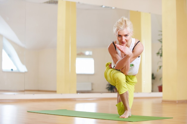 Beautiful sporty fit yogi woman practices yoga asana vatayanasana horse face pose in the fitness room