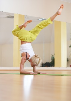 Beautiful sporty fit yogi woman practices yoga asana vrischikasana scorpion pose in the fitness room